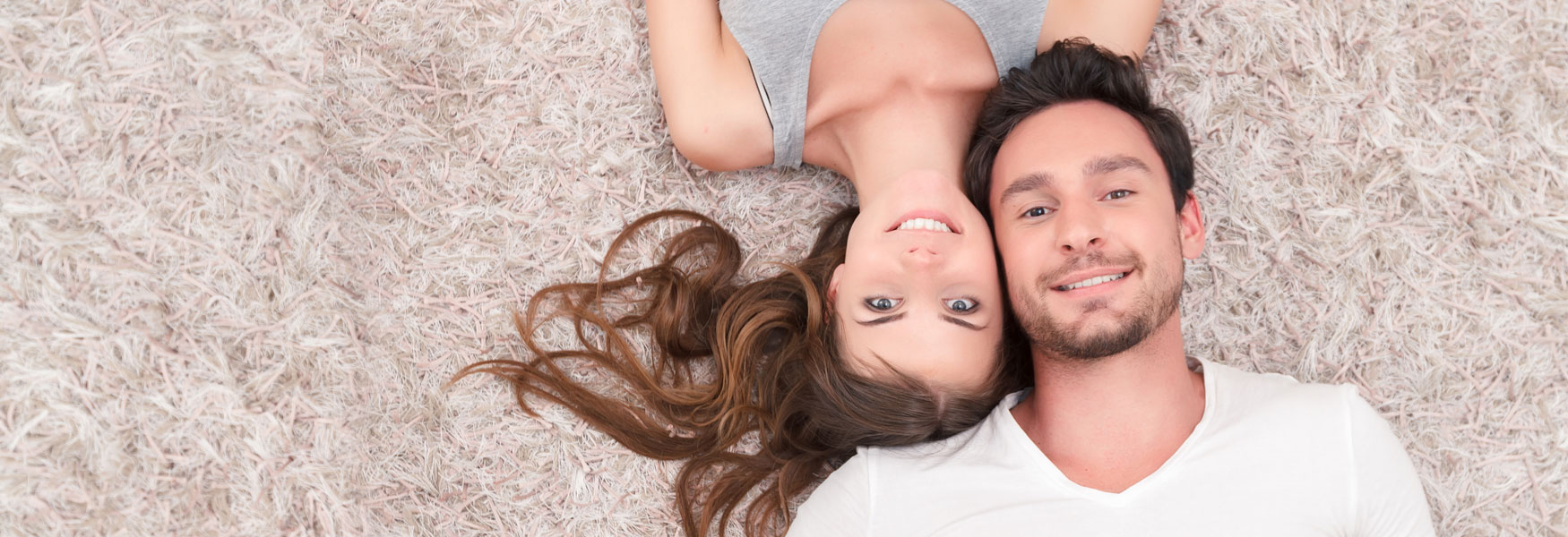 Smiling couple lay down on floor facing up.